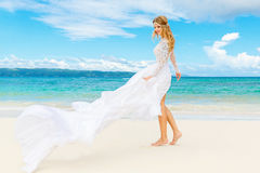 Beautiful blond bride in white wedding dress with big long train Stock Photos