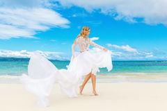 Beautiful blond bride in white wedding dress with big long train Stock Photography
