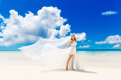 Beautiful blond bride in white wedding dress with big long white Royalty Free Stock Image