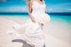 Beautiful blond bride in white wedding dress with white wedding bouquet stand on sea shore. Tropical turquois sea on the backgroun Stock Images