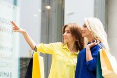 Beautiful blond and brunette shopaholic women Royalty Free Stock Image