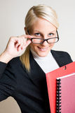 Beautiful blond businesswoman. Portrait of beautiful friendly smiling businesswoman peeking over her glasses Royalty Free Stock Photography