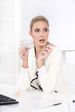 Beautiful blond businesswoman is shocked - making nail manicure Royalty Free Stock Photos