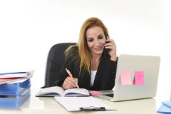 Beautiful blond businesswoman talking on mobile phone smiling holding pen writing notes on notepad Stock Photos