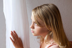 Beautiful blond Caucasian girl looking in a window Royalty Free Stock Image