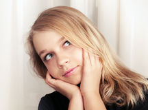 Beautiful blond Caucasian girl looks up with smile Stock Images