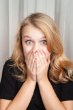 Beautiful blond Caucasian surprised girl covers her mouth. Beautiful blond Caucasian surprised girl opened her eyes wide and covers her mouth with her hands Royalty Free Stock Photos