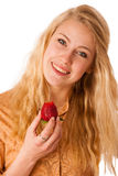 Beautiful blond cheerful caucasian woman eats a big red strawber Royalty Free Stock Image