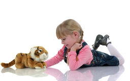 Beautiful blond child. With braids and pink dress sitting on the floor plays with a toy stock images