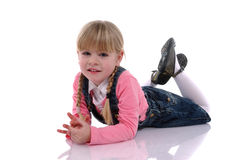 Beautiful blond child. With braids and pink dress sitting on the floor stock photography