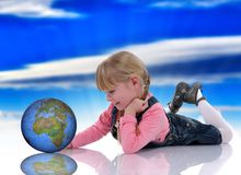 Beautiful blond child. With world map and pink dress sitting on the floor stock images