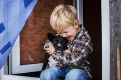 Beautiful blond child embrace his dog. Friendship between human and animal Royalty Free Stock Photos