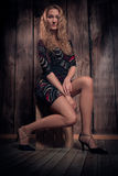 Beautiful blond curly hair model sitting in a pose on the box over wooden wall background Royalty Free Stock Image