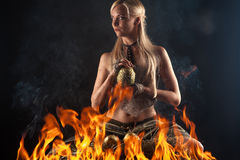 Beautiful blond with a dragon egg in hands in the fire Stock Photo