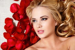 Beautiful blond dreaming girl with red roses Stock Images