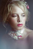 Beautiful blond fashion girl with flowers on neck and in her hair, wet Nude makeup. Beauty face. Stock Photo