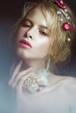Beautiful blond fashion girl with flowers on neck and in her hair, wet Nude makeup. Beauty face. Royalty Free Stock Photo