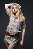 Beautiful blond fashion model with blowing hair. On dark background Royalty Free Stock Photography