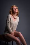 Beautiful blond fashion model, seated, in stretchy knitwear top Royalty Free Stock Photography