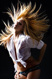 Beautiful blond female with flying hair dancing royalty free stock image