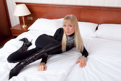 Beautiful blond female model in black tight glamorous outfit, fa. Gorgeous blond female model with blue eyes in black tight glamorous outfit, fancy leather boots Stock Photography