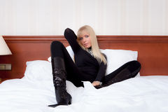 Beautiful blond female model in black tight glamorous outfit, fa. Gorgeous blond female model with blue eyes in black tight glamorous outfit, fancy leather boots Royalty Free Stock Photos
