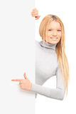 A beautiful blond female pointing on a panel Royalty Free Stock Photo