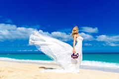 Beautiful blond fiancee in white wedding dress with big long white train and with wedding bouquet stand on shore sea.  royalty free stock photos