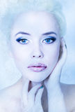 Beautiful blond frozen bride on a blue background with professional make-up royalty free stock images
