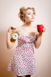 Beautiful blond funny pinup girl with curlers holding golden alarm-clock & cup of hot drink looking at camera portrait Stock Image