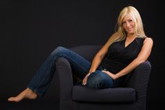 Beautiful blond girl. Sexy blond girl sitting relaxed isolated on black background Royalty Free Stock Photo