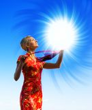 Beautiful blond girl. With a magic light sphere over crystal clear blue sky Royalty Free Stock Photos