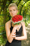 Beautiful blond girl. In evening dress holding bouquet of red roses Stock Images
