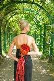 Beautiful blond girl. In black evening dress with a bouquet of red roses Royalty Free Stock Images