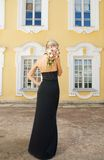 Beautiful blond girl. In black evening dress with a boquet Stock Image