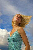 Beautiful blond girl. And blue cloudy sky behind her Stock Images