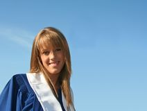 Beautiful blond girl. In graduation gown Royalty Free Stock Photo