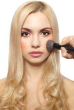 Beautiful blond girl applying make up Stock Photography