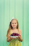 Beautiful blond girl on a background of turquoise wall holding plate with cherry. Stock Photo