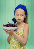 Beautiful blond girl on a background of turquoise wall holding plate with cherry. Royalty Free Stock Image