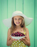 Beautiful blond girl on a background of turquoise wall in the white hat holding plate with cherry. Royalty Free Stock Image