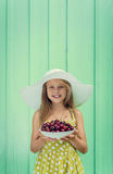 Beautiful blond girl on a background of turquoise wall in the white hat holding plate with cherry. Stock Images