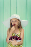 Beautiful blond girl on a background of turquoise wall in the white hat holding plate with cherry. Royalty Free Stock Photography