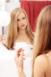 The beautiful blond girl in a bathroom. The beautiful blond girl looks in a mirror in a bathroom stock images