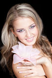 Beautiful blond girl with big pink flower in hands Stock Image