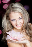 Beautiful blond girl with big pink flower in hands Royalty Free Stock Photo