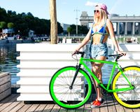 Beautiful blond girl in bikini and denim shorts posing in city park with fashionable bicycle fix. Royalty Free Stock Image