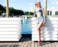 Beautiful blond girl in bikini and jeans shorts posing in city park on a warm summer evening Royalty Free Stock Images