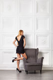 Beautiful blond girl in black dress near armchair Stock Photo