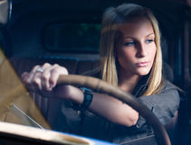 Beautiful blond girl in a black vintage car. Beautiful young blond girl smiling in a black vintage car, holding the steering wheel, shot through the windscreen stock photo
